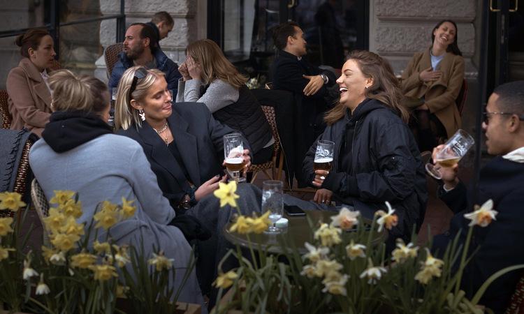 Khách hàng nói chuyện ngoài một quán bar ở thủ đô Stockholm ngày 8/4. Ảnh: AP.