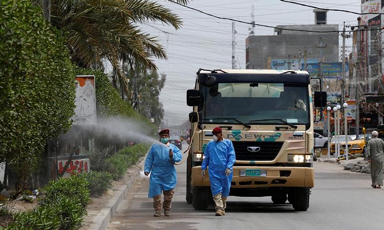Binh sĩ quân đội Iraq mặc đồ bảo hộ, phun khử trùng trên đường phố Baghdad, Iraq, ngày 31/3. Ảnh: Reuters.