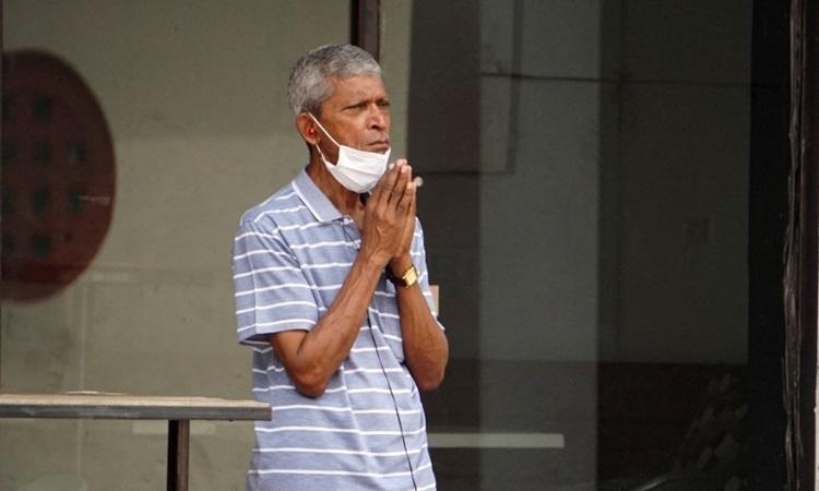 Người đàn ông đeo khẩu trang quanh cằm đứng chắp tay đối diện ngôi đền Hindu ở phố người Hoa, Singapore hôm 13/4. Ảnh: AFP.