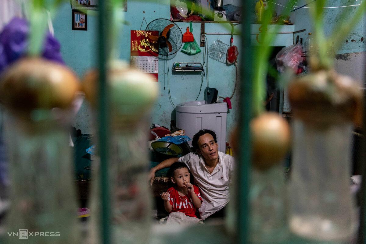 Cường và con trai út trong phòng trọ, những ngày giãn cách xã hội tháng 4. Ảnh: Thanh Huế.