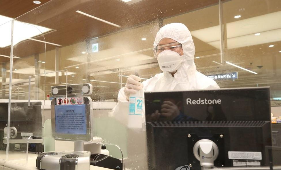 Nhân viên di trú khử trùng quầy làm việc tại sân bay quốc tế Incheon, Hàn Quốc, sau khi đón các hành khách quốc tế hôm 8/4. Ảnh: Yonhap