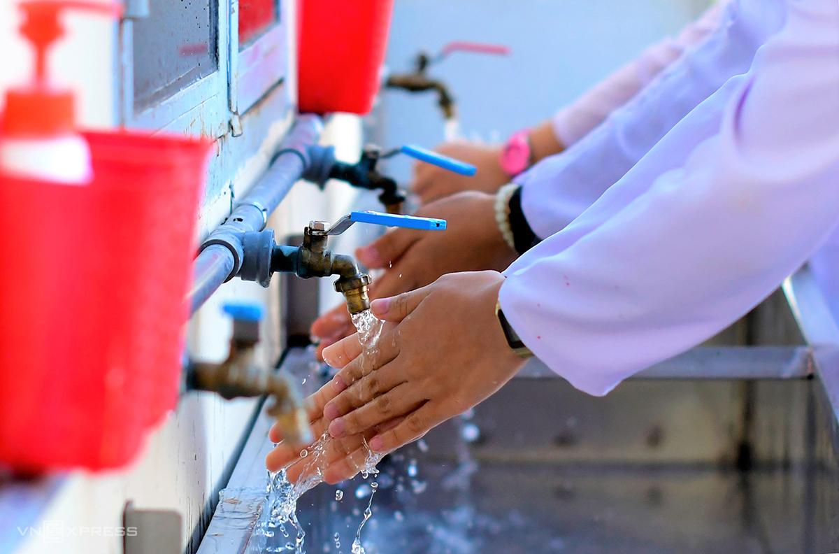 Học sinh rửa tay sát khuẩn trước khi vào lớp học. Ảnh: Khánh Hưng.