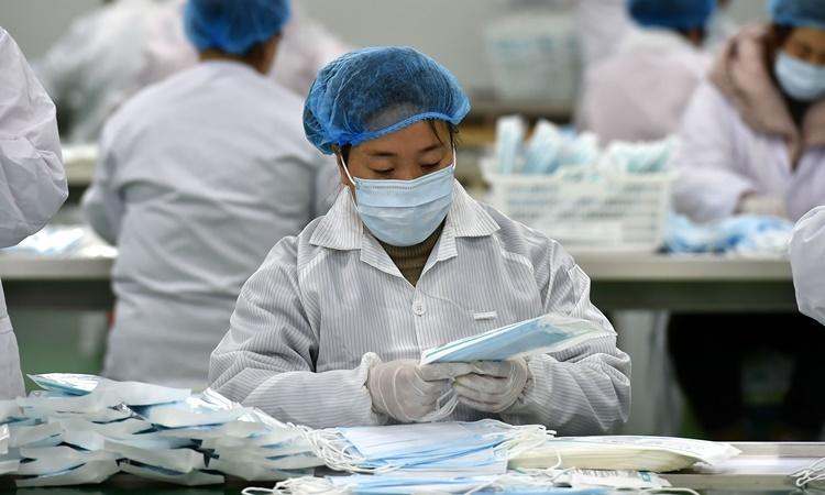 Nhân viên làm việc tại một nhà máy sản xuất khẩu trang ở phía bắc tỉnh Sơn Tây, Trung Quốc, ngày 25/2. Ảnh: Xinhua.