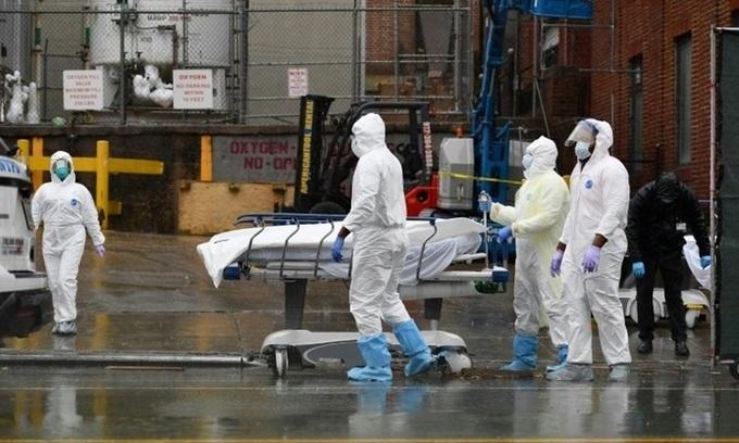 Nhân viên y tế di chuyển một bệnh nhân đã chết tới xe tải đông lạnh tại Bệnh viện Trung tâm Brooklyn ở New York hôm 9/4. Ảnh: AFP.