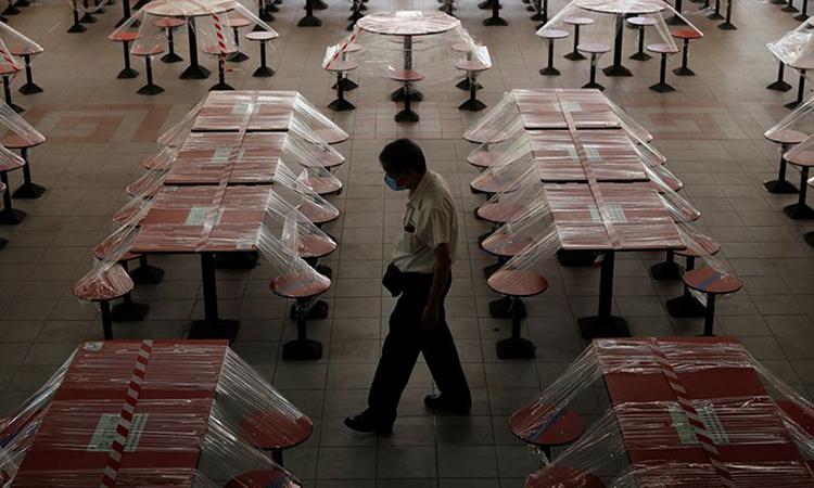 Người đàn ông đeo khẩu trang đi qua một nhà hàng đóng cửa tại khu ẩm thực trên phố người Hoa ở Singapore ngày 17/4. Ảnh: Reuters.