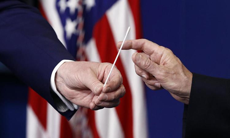 Tổng thống Mỹ Trump (trái) và Phó tổng thống Mike Pence cầm một mẫu gạc có thể dùng trong xét nghiệm nCoV tại họp báo ở Nhà Trắng hôm 19/4. Ảnh: AP.