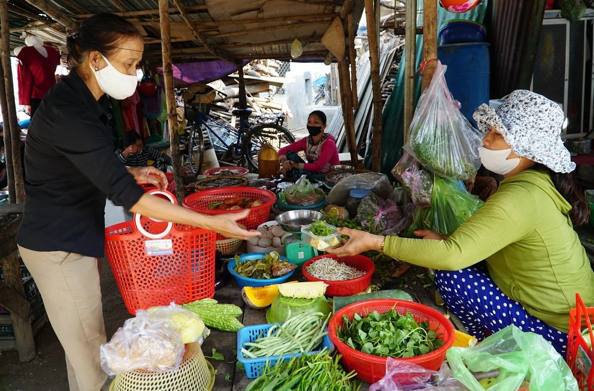 Bà Kim Hoa đến hàng rau ở chợ quê Châu Ổ, huyện Bình Sơn, mua thức ăn giùm người già. Ảnh: Phạm Linh.