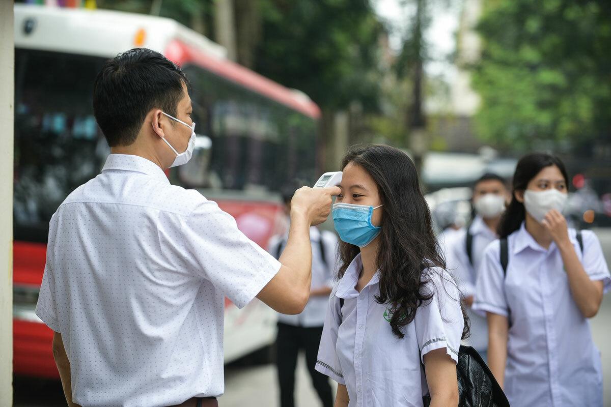 Giáo viên đo thân nhiệt tại cổng trường THPT Tô Hiến Thành. Ảnh: Lê Hoàng.