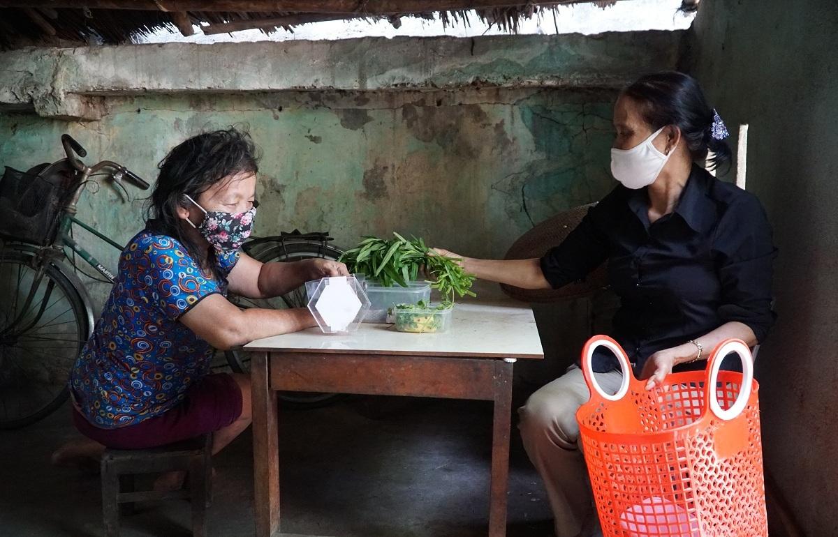 Bà Kim Hoa giao thức ăn sau khi đi chợ giùm cho bà Lựu (trái). Ảnh: Phạm Linh.