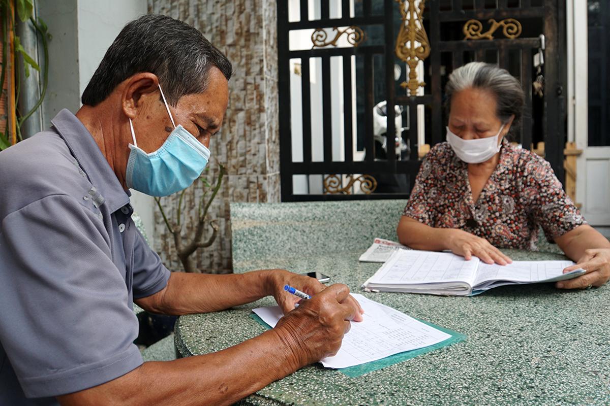 Ông Võ Văn Kính trao đổi với chủ nhà trọ, xác định người thuê phòng thuộc diện được nhận hỗ trợ. Ảnh: Mạnh Tùng.