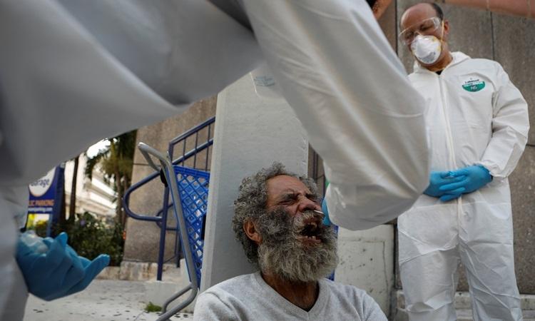 Một người đàn ông vô gia cư ở thành phố Miami, bang Florida được lấy mẫu xét nghiệm Covid-19 hôm 16/4. Ảnh: Reuters.