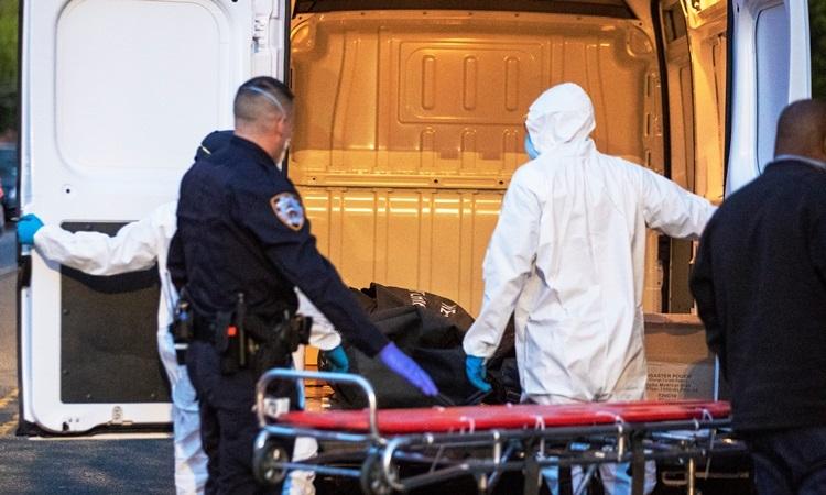 Một cảnh sát giúp nhân viên y tế đưa thi thể bệnh nhân Covid-19 khỏi một ngôi nhà ở thành phố New York, Mỹ hôm 20/4. Ảnh: Reuters.