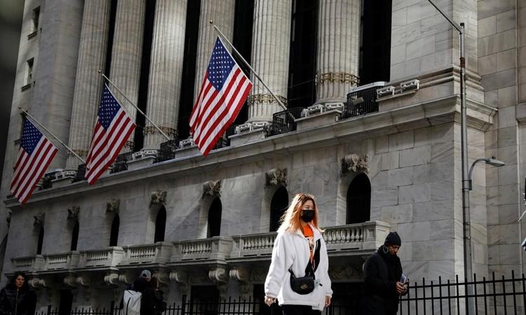 Người phụ nữ đeo khẩu trang đi qua Sàn Chứng khoán New York ngày 4/3. Ảnh: Reuters.