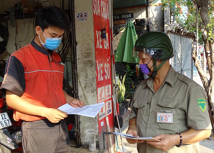 Ông Đinh Quốc Anh phát mẫu kê khai thông tin cho một chủ tiệm sửa xe trên địa bàn. Ảnh: Hà An
