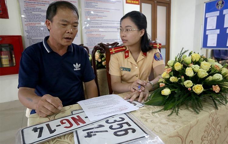 Người dân làm thủ tục đăng ký biển số ở Cục CSGT-Bộ Công an. Ảnh:Bá Đô.