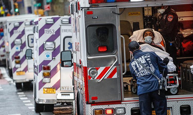 Nhân viên y tế đưa bệnh nhân Covid-19 xuống xe cứu thương bên ngoài Trung tâm Y tếNYU Langone, New York, ngày 13/4. Ảnh: AP.