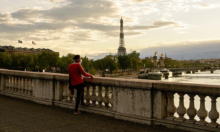 Người phụ nữ đứng ngắm dòng sông Seine, thành phố Paris, Pháp, ngày 17/4. Ảnh: NYTimes.