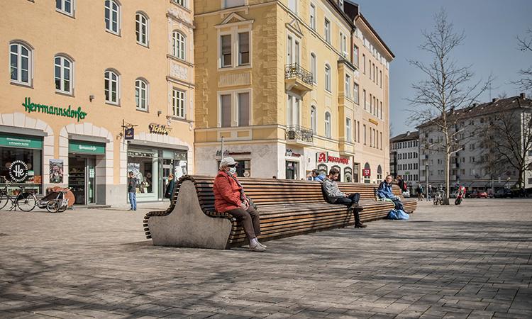 Ngươi dân Đức giữ khoảng cách an toàn khi ngồi trên băng ghế tại một quảng trường ở thành phốMunich, Đức, tháng này. Ảnh: NYTimes.