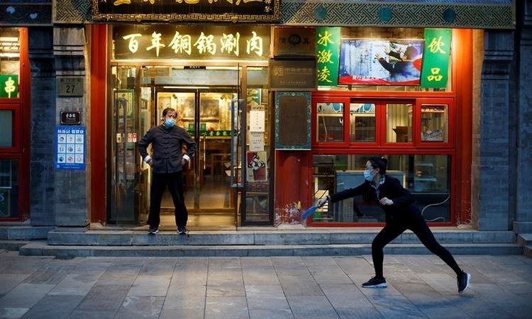Nhân viên tại một nhà hàng ở Bắc Kinh chơi cầu lông nhân lúc vắng khách ngày 8/4. Ảnh: Reuters.