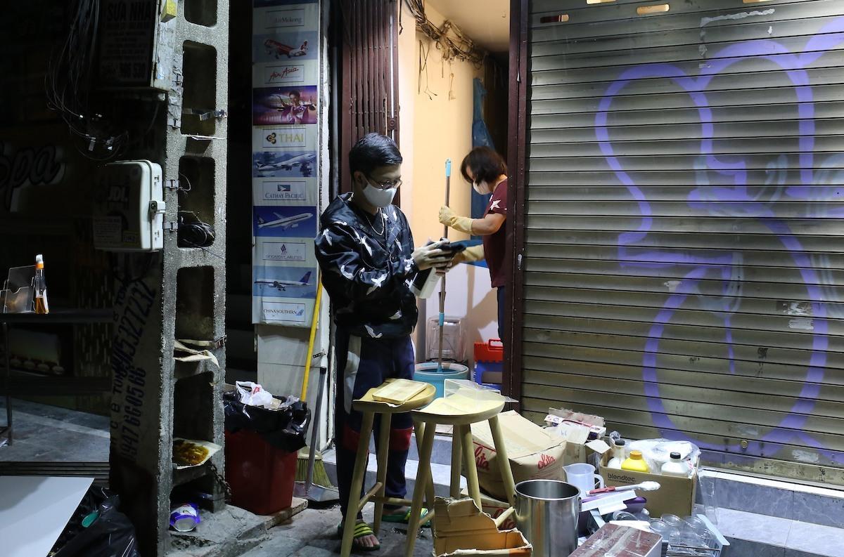 Anh Nguyễn Chí Thanh chuẩn bị đồ mở lại cửa hàng trên phố Đinh Liệt. Ảnh: Tất Định