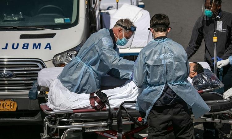 Nhân viên y tế chăm sóc cho bệnh nhân nhiễm nCoV bên ngoài một bệnh viện ở Bronx, New York. Ảnh: AFP.