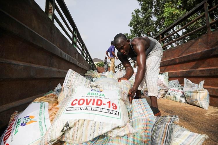 Một thanh niên dỡ bao tải gạo viện trợ để phân phát cho người bị ảnh hưởng bởi Covid-19 tại Abuja, Nigeria, hôm 17/4. Ảnh: Reuters.