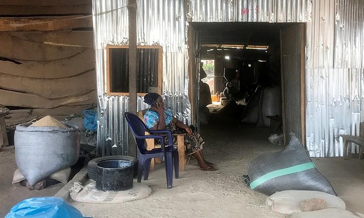 Mercy Yialase ngồi trước xưởng xay xát gạo ở Wurukum trong thành phố Makurdi, bang Benue, Nigeria, hôm 13/4. Ảnh: Reuters.