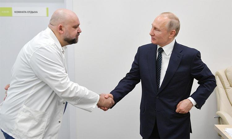 Tổng thống Nga Vladimir Putin (phải) bắt tay với  Denis Protsenko (trái), giám đốc bệnh viện Kommunarka chuyên điều trị cho người nhiễm nCoV ở ngoại ô Moskva, trong chuyến thăm hôm 24/3. Ảnh: Điện Kremlin.