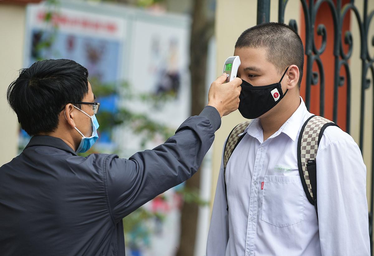Học sinh THPT ở Thanh Hoá được kiểm tra thân nhiệt khi vào trường trong ngày đầu tiên đi học trở lại hôm 21/4. Ảnh: Lê Hoàng.