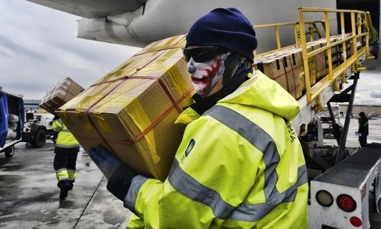 Nhân viên mặt đất tại sân bay quốc tế Los Angeles, Mỹ, bốc dỡ các thùng chứa đồ bảo hộ y tế từ máy bay chở hàng của hãng hàng không China Southern Airlines ngày 10/4. Ảnh: AP.