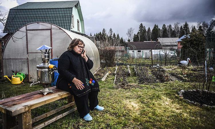 Nataliya Sapiga nói chuyện điện thoại bên vườn rau trong căn nhà của cô ở ngoại ô Moskva. Ảnh: AFP.