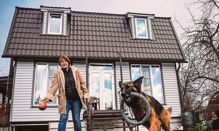 Nataliya chơi đùa cùng chú chó trong sân căn nhà ở ngoại ô Moskva. Ảnh: AFP.