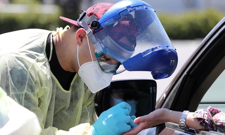 Nhân viên y tế tại một trạm xét nghiệm ởLos Angeles ngày 24/4. Ảnh: Reuters.