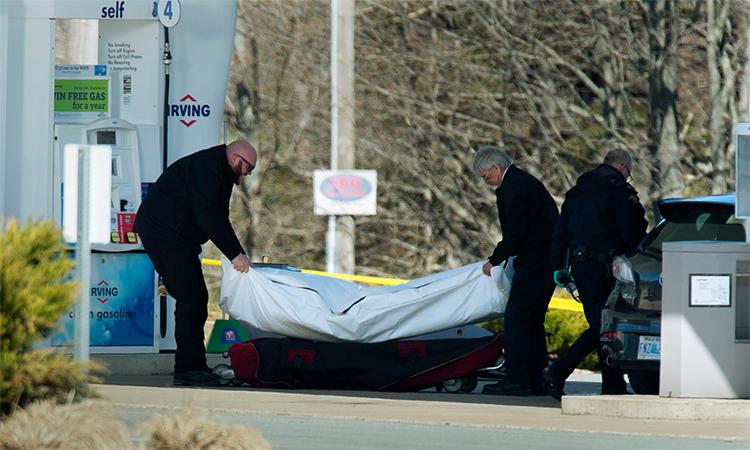 Nhân viên pháp y đưa thi thể một nạn nhân khỏi cây xăng ở Enfield, Nova Scotia, Canada, ngày 19/4. Ảnh: AP.