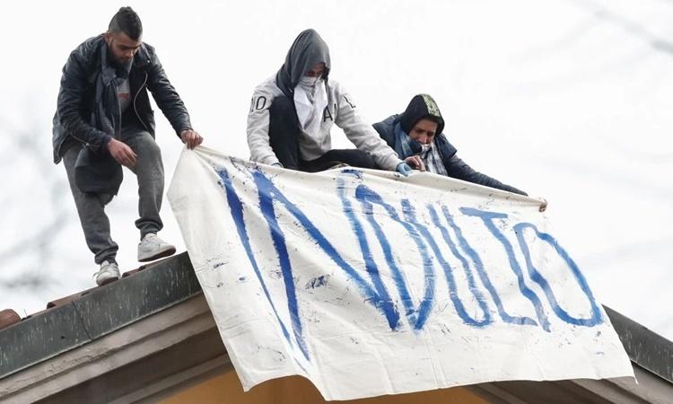 Các phạm nhân trèo lên mái nhà trong cuộc bạo loạn tại nhà tù San Vittore, Italy, ngày 9/3. Ảnh: AP.