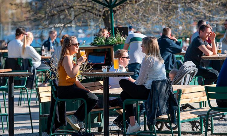 Khách dùng đồ uống và trò chuyện tại một quán ngoài trời ở thủ đô Stockholm, Thụy ĐIển, ngày 22/4. Ảnh: AFP.