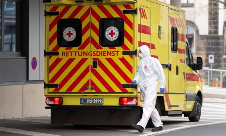 Nhân viên y tế mặc đồ bảo hộ đi gần xe cứu thương chở bệnh nhân nhiễm nCoV từ Italy tới điều trị tại Bệnh viện Đại học Dresden, Đức, ngày 26/3. Ảnh: Reuters.