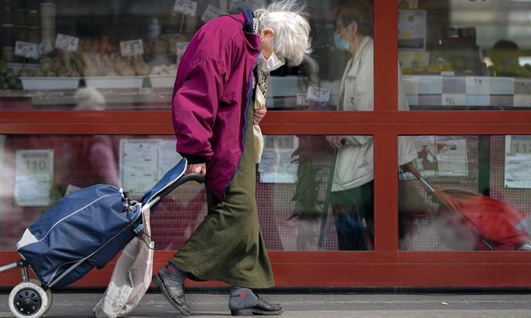 Một phụ nữ đi chợ ởBucharest, Romania ngày 21/4. Ảnh: AP.
