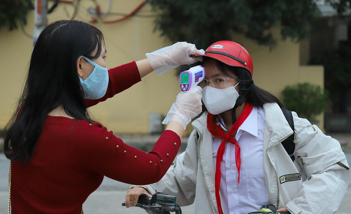 Học sinh được đo thân nhiệt tại cổng trường THCS Nguyễn Du, phường Bắc Hà, thành phố Hà Tĩnh. Ảnh: Đức Hùng