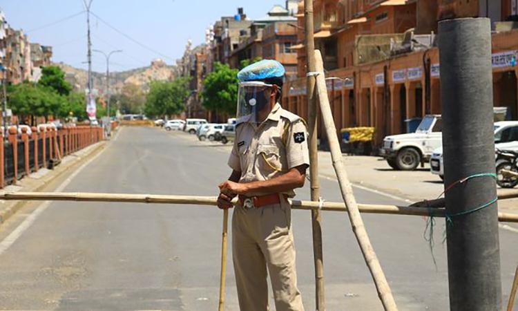 Một cảnh sát làm nhiệm vụ ở bang Rajasthan, Ấn Độ, đang áp lệnh phong tỏa ngăn Covid-19. Ảnh: PA.