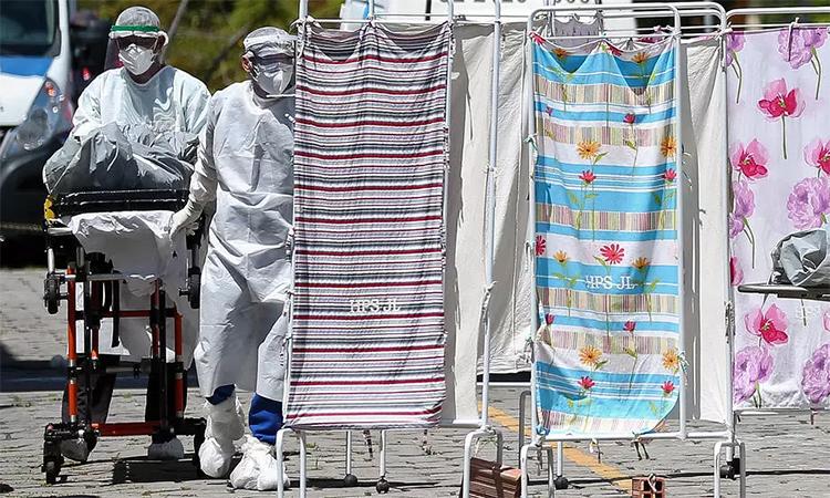 Nhân viên y tế mặc trang phục bảo hộ di chuyển thi thể người chết vì nCoV tại Bệnh viện Joao Lucio, Manaus, Brazil, ngày 21/4. Ảnh: AFP.