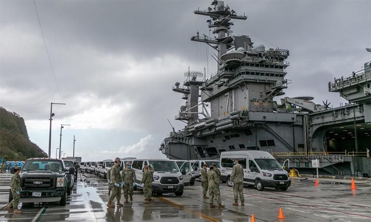 Binh sĩ Mỹ tham gia đưa các thủy thủ không nhiễm nCoV rời tàu sân bay USS Theodore Roosevelt tới khu cách ly tại căn cứ hải quân Guam, ngày 3/4. Ảnh: US Navy.