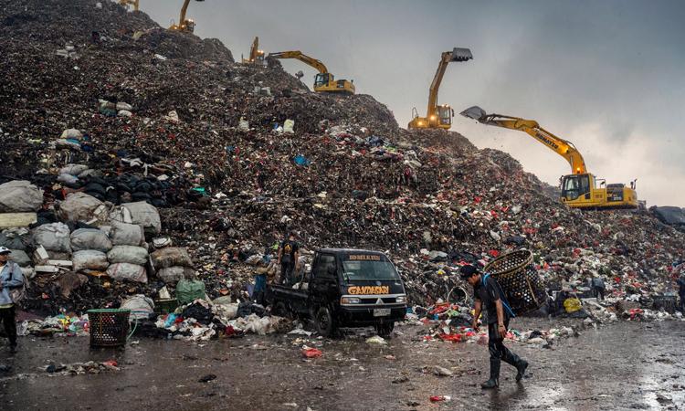 Người đàn ông đeo giỏ đi nhặt rác giữa trời mưa ở bãi rácBantar Gebang,Bekasi, Tây Java, tháng này. Ảnh: NYTimes.