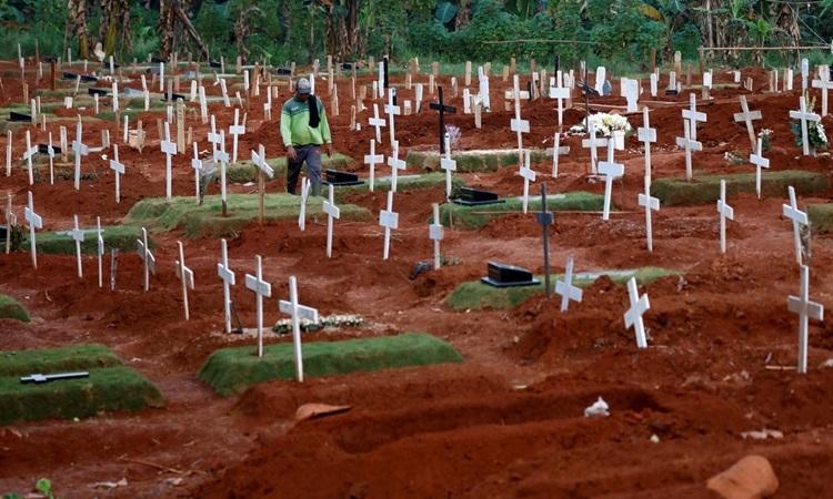 Một công nhân đô thị đi bộ giữa các ngôi mộ tại khu nghĩa trang dành cho nạn nhân Covid-19 tại Jakarta, Indonesia hôm 22/4. Ảnh: Reuters.