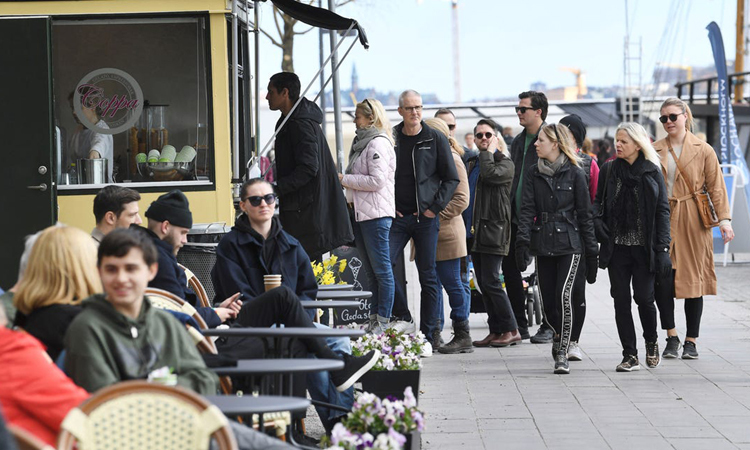 People queue to buy ice cream in Norr Malarstrand street, Stockholm, April 19. Photo: TT News Agency.