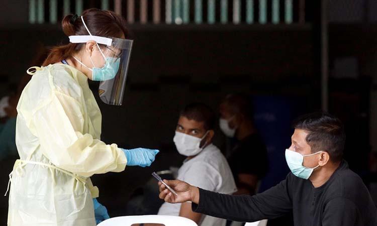 Chuyên gia y tế trò chuyện với người lao động nhập cư tại một khu ký túc xá ở Singapore hôm 27/4. Ảnh: Reuters.