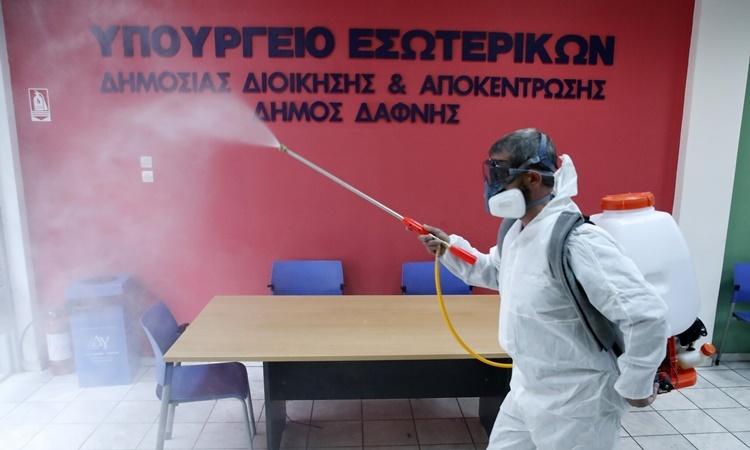 Nhân viên trong trang phục bảo hộ phun chất khử trùng tại một phòng tiếp dân ở khu ngoại ô Dafni, phía đông thủ đô Athens, Hy Lạp, ngày 9/3. Ảnh: AP.