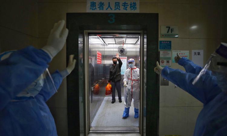 Nhân viên y tế vẫy tay chào bệnh nhân Covid-19 xuất viện tại Bệnh viện Hội Chữ thập đỏ Vũ Hán, hồi tháng 3. Ảnh: AFP.