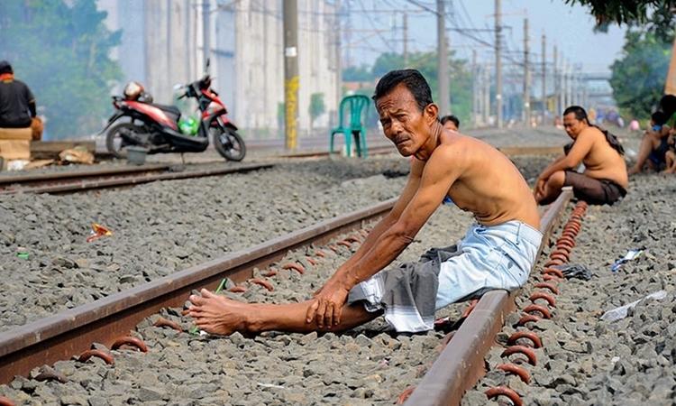 Người Indonesia ngồi trên đường ray tàu hỏa tắm nắng ở Bekasi, Tây Java, hôm 4/4. Ảnh: AFP.