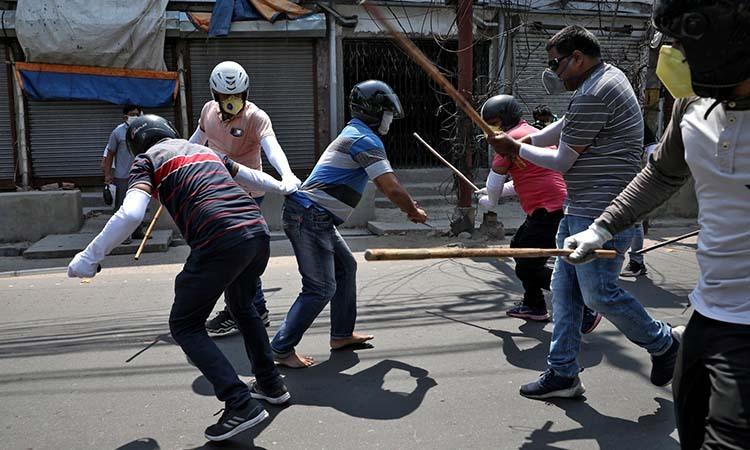 Cảnh sát mặc thường phục đánh một người đàn ông vì vi phạm lệnh phong tỏa ở ngoại ô thành phố Kolkata, Ấn Độ hôm 19/4. Ảnh: Reuters.